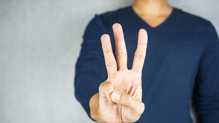 3本の指を見せる人