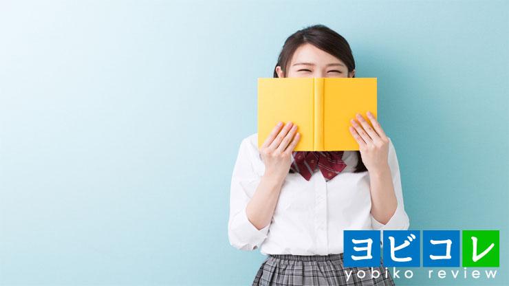 本で顔を隠す女子高生
